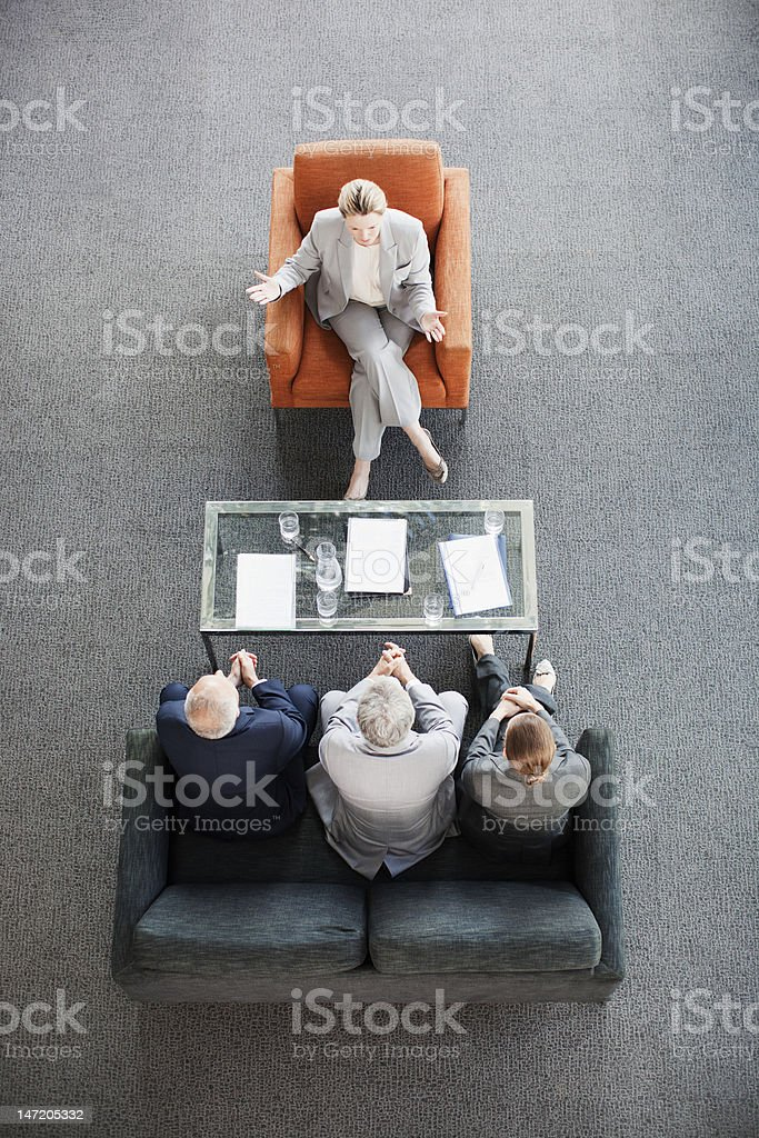 Businesswoman leading meeting with co-workers in lobby stock photo