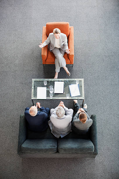 Businesswoman leading meeting with co-workers in lobby  persuasion stock pictures, royalty-free photos & images
