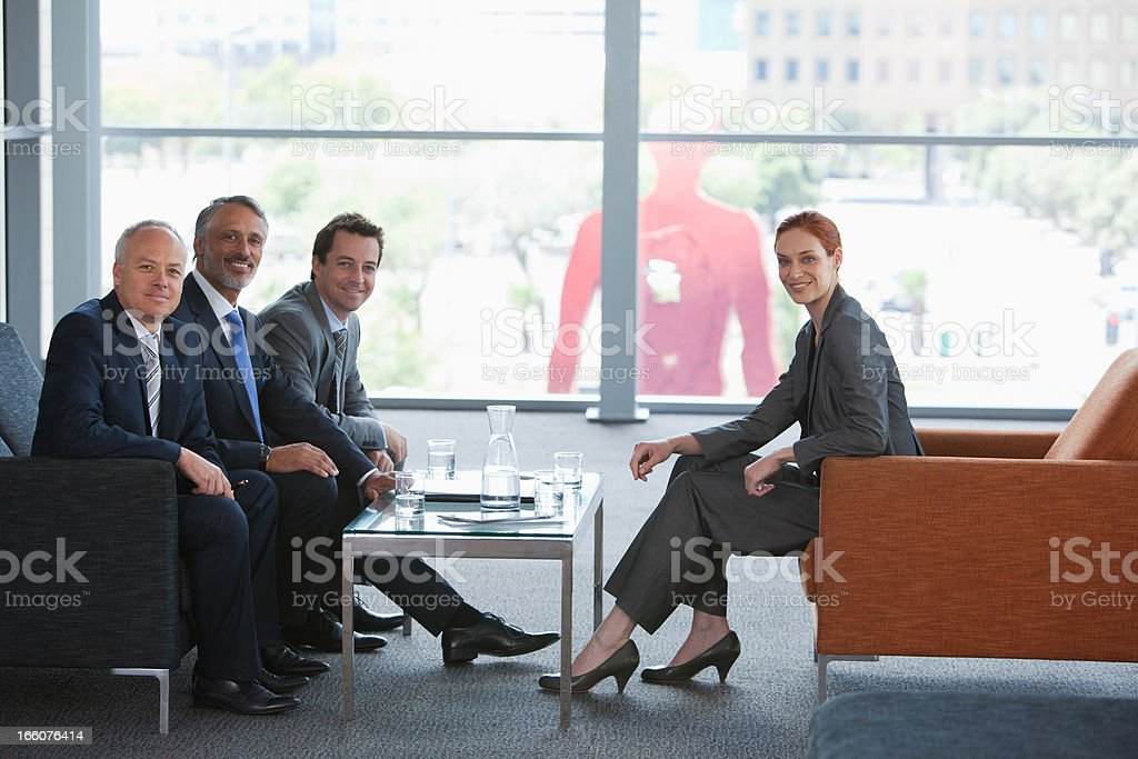 Businesswoman leading meeting with co-workers in lobby royalty-free stock photo