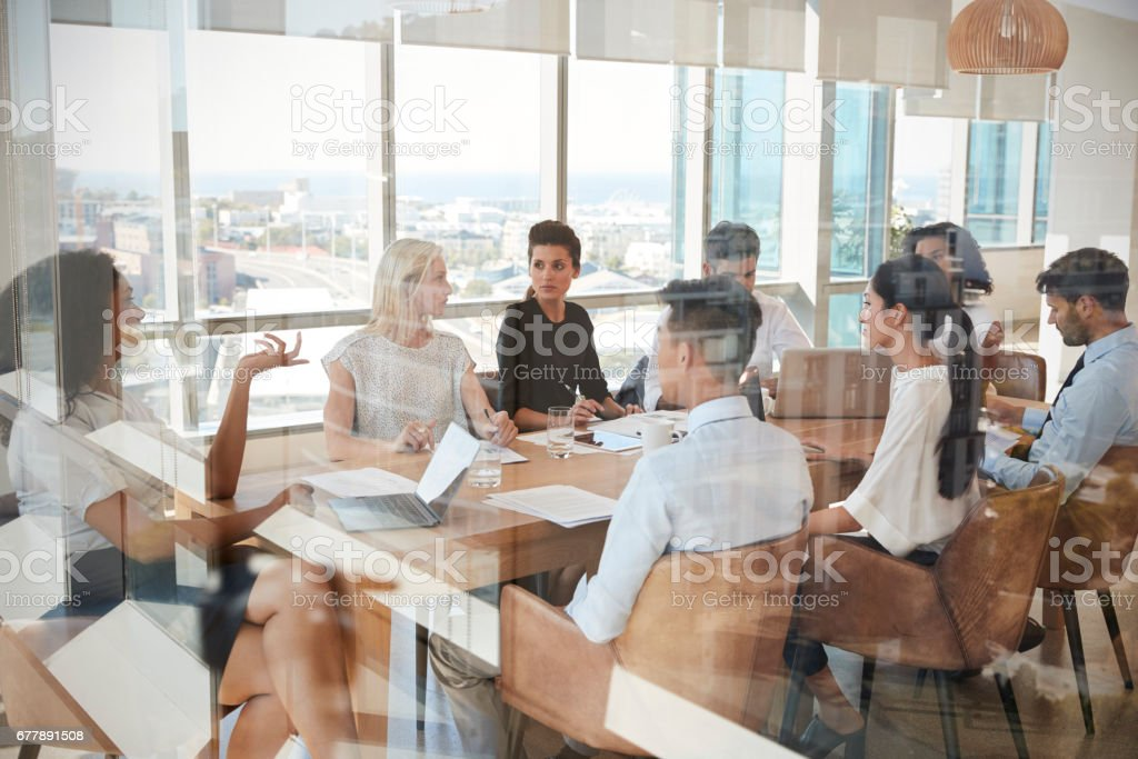 Businesswoman Leads Meeting Around Table Shot Through Door royalty-free stock photo