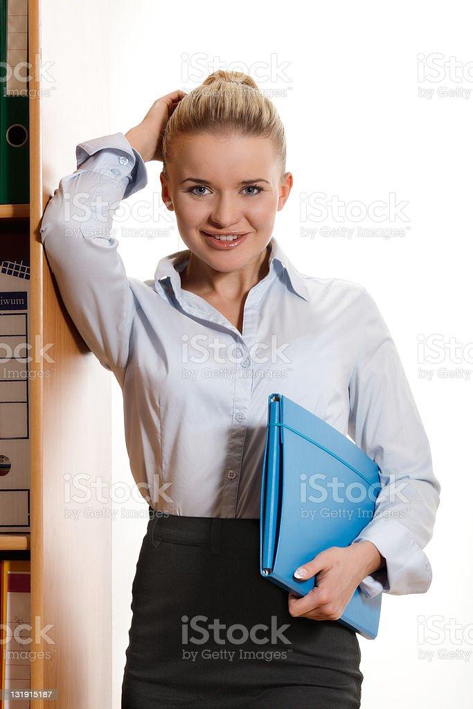 Businesswoman leaning against bookshelf stock photo