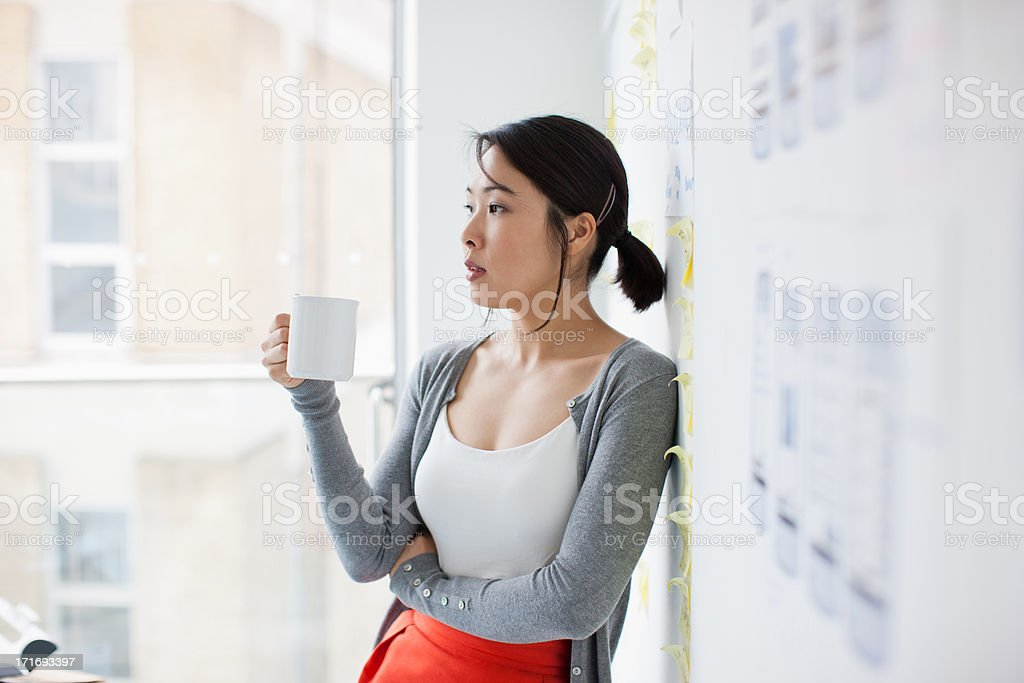 Businesswoman leaning against whiteboard and drinking coffee stock photo