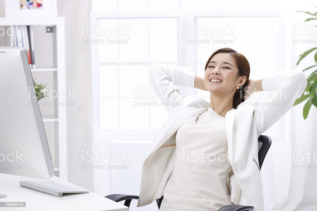 A businesswoman leaning back in her chair at her desk stock photo