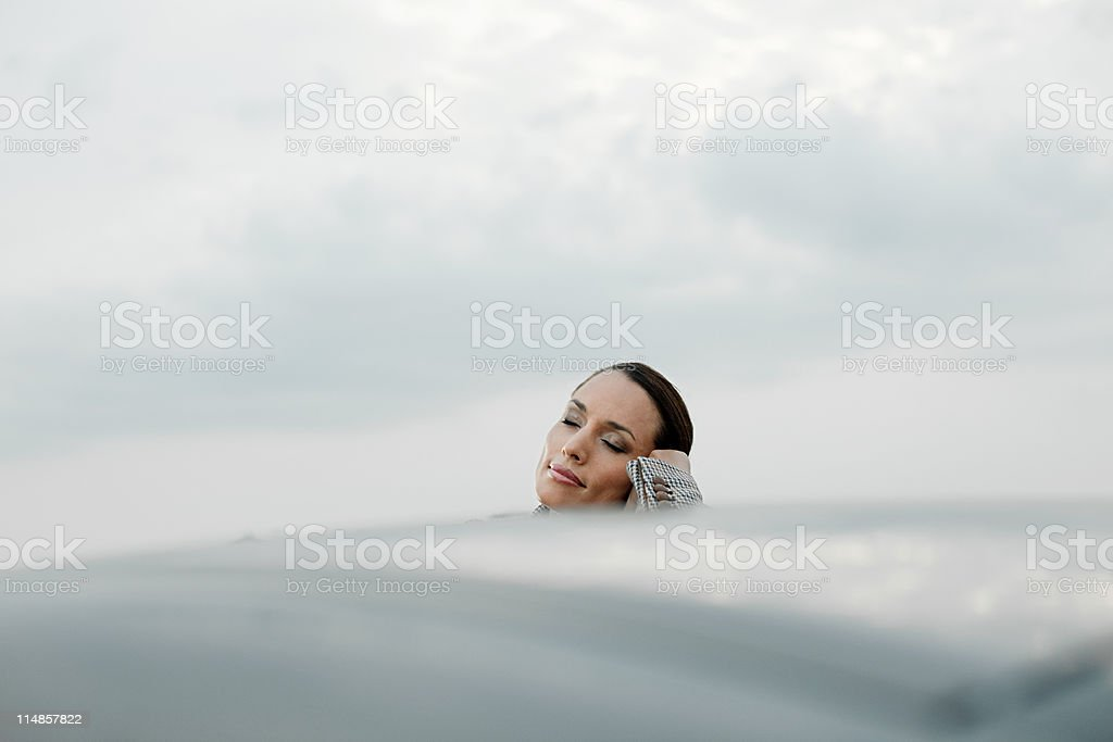 Businesswoman leaning on car roof with eyes closed stock photo