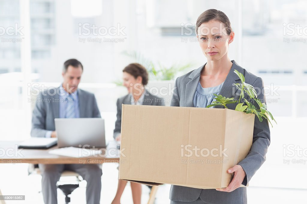 Businesswoman leaving office after being fired stock photo