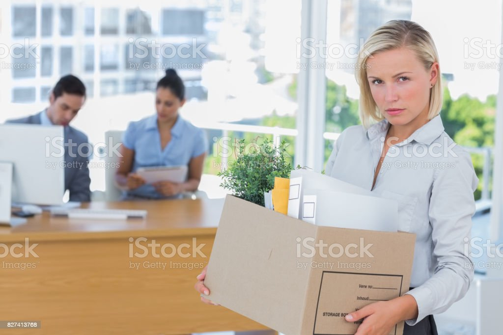 Businesswoman leaving office after being laid off and looking at camera stock photo
