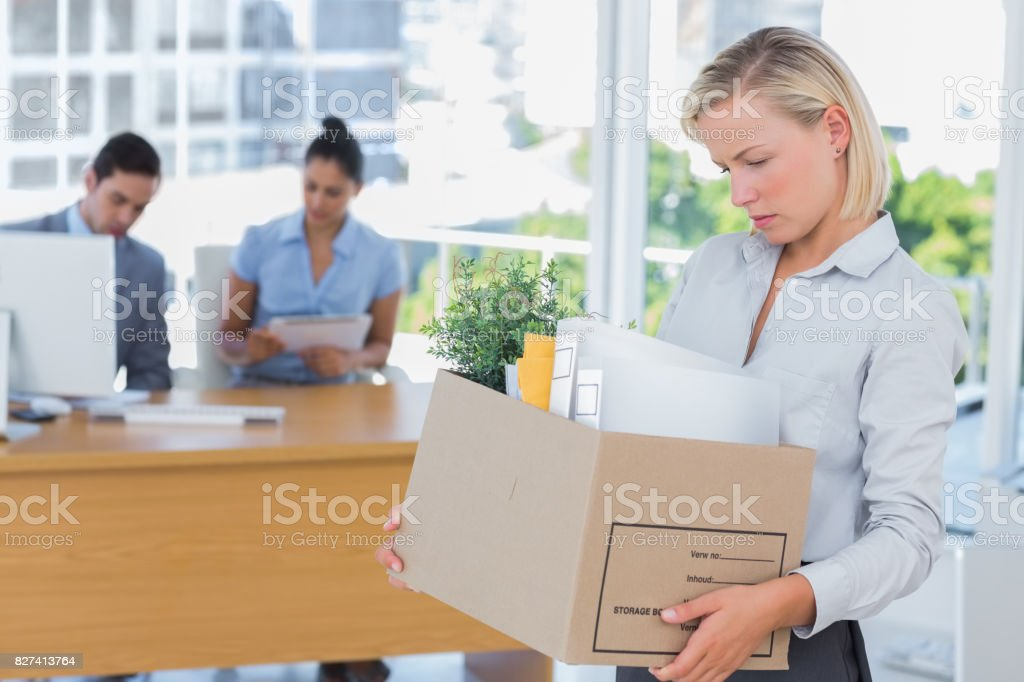 Businesswoman leaving office after being laid off stock photo