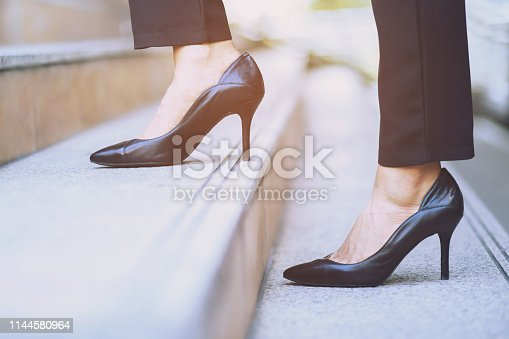 Businesswoman legs walking the stairs in modern city.