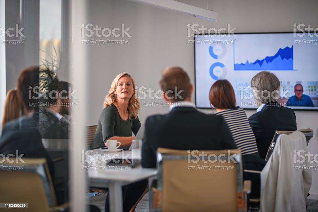 Businesswoman Listening to Associate During Video Conference Rear view personal perspective of diverse executive team video conferencing with male CEO and discussing data. Board Room Stock Photo