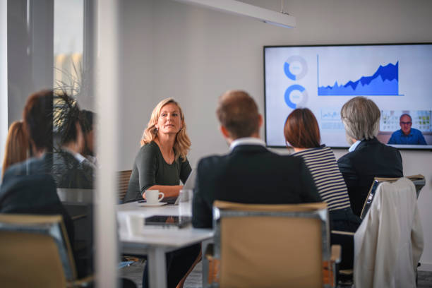 Businesswoman Listening to Associate During Video Conference Rear view personal perspective of diverse executive team video conferencing with male CEO and discussing data. board room stock pictures, royalty-free photos & images