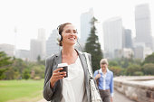 istock Businesswoman listening to headphones and carrying coffee 170219703