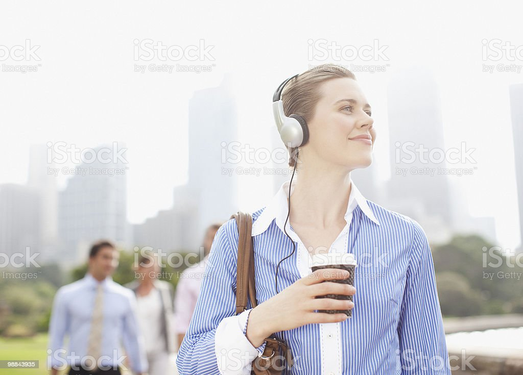 Businesswoman listening to headphones and carrying coffee royalty free stockfoto
