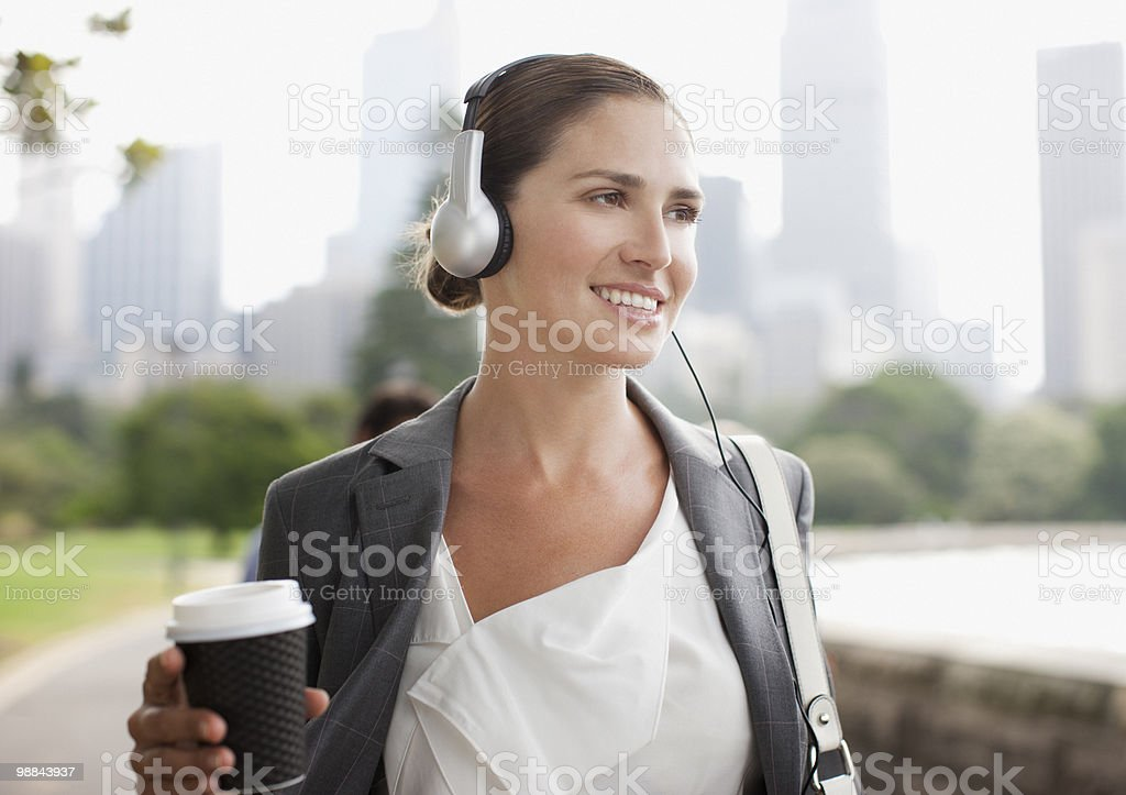 Businesswoman listening to headphones and carrying coffee stock photo