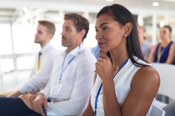 Businesswoman listening to speaker in business seminar Side view of caucasian Businesswoman listening to speaker in business seminar at conference meeting. International diverse corporate business partnership concept attending stock pictures, royalty-free photos & images