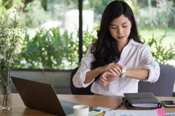 Geschäftsfrau Blick auf ihre Uhr am Arbeitsplatz. Start-up Frau Prüfzeit auf Armbanduhr im Büro.  junge Unternehmerin mit Papierkram auf Tisch. – Foto