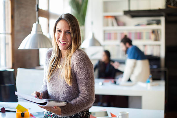 businesswoman looking and smiling at camera in small office. - 30 39 years stock photos and pictures