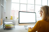 Back view portrait of unrecognizable businesswoman using computer sitting at desk in office, copy space