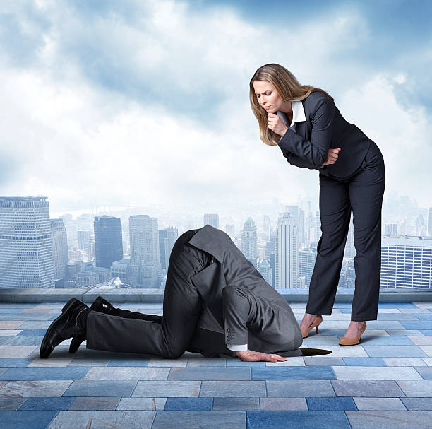 Businesswoman Looking At Businessman Who Has Head Buried In Hole A businesswoman looks down with concern at a businessman who is crouching on all fours as he buries his head in a hole.  She is concerned that he is avoiding the responsibilities of his job.  In the background is the skyline of a major urban city. head in the sand stock pictures, royalty-free photos & images