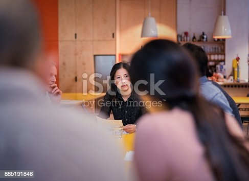 Mature businesswoman looking at colleagues in cafe. Multi-ethnic business people are discussing in coffee shop. Male and female professionals are sitting in restaurant.