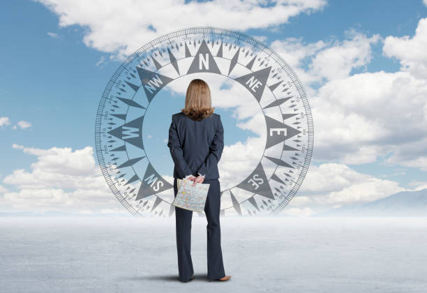Businesswoman Looking At Compass On Horizon stock photo
