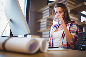 Businesswoman looking at computer while drinking water on creative office