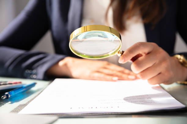 Businesswoman Looking At Contract Form Through Magnifying Glass Close-up Of A Businesswoman's Hand Looking At Contract Form Through Magnifying Glass magnifying glass stock pictures, royalty-free photos & images