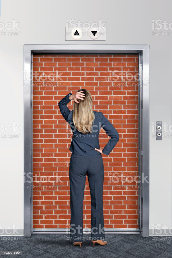 Businesswoman Looking At Elevator Blocked By Brick Wall stock photo