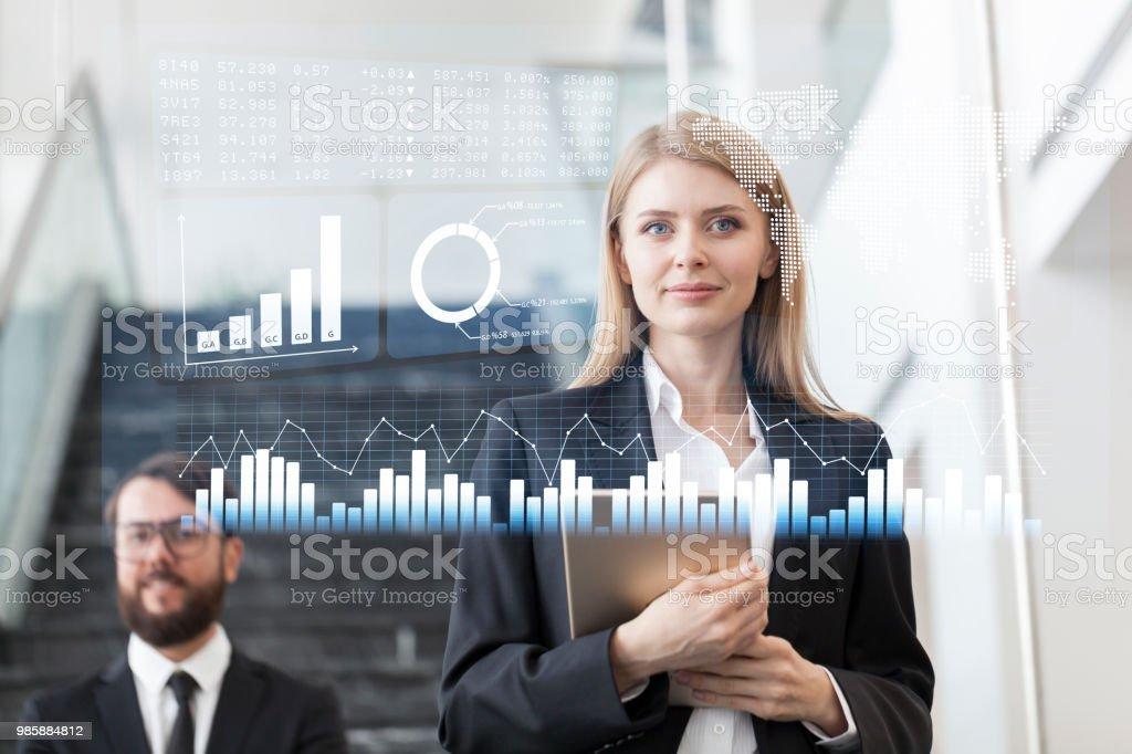 Mulher de negócios olhando dados financeiros em exposição futurista - foto de acervo