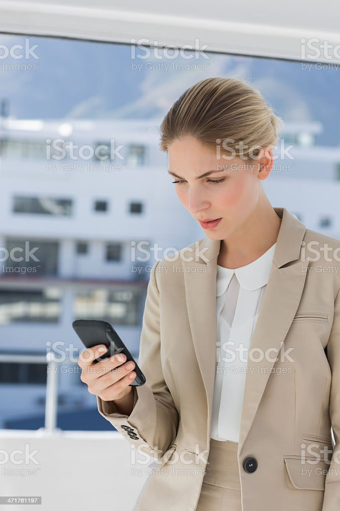 Businesswoman looking at her smartphone royalty-free stock photo