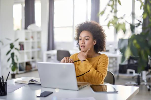 Geschäftsfrau schaut sich Laptop an, während sie im Büro sitzt. – Foto