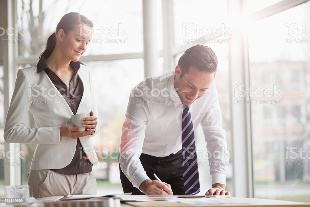 Businesswoman looking at male colleague writing notes at desk stock photo