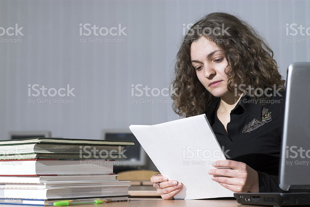 Businesswoman looking at papers in front of computer royalty-free stock photo