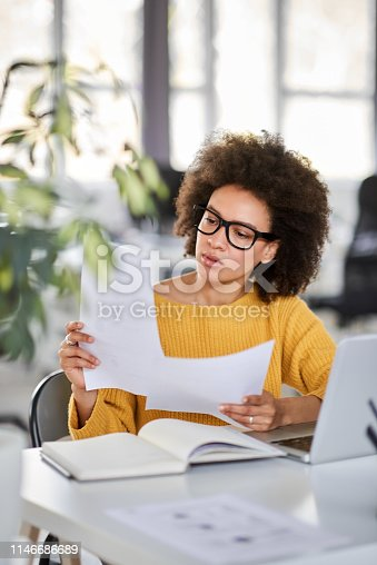 istock Businesswoman looking at paperwork. 1146686689