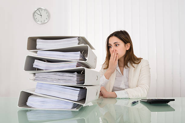 businesswoman looking at pile of document - 出勤 ストックフォトと画像