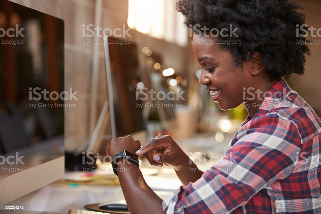 Businesswoman Looking At Smart Watch In Design Office stock photo