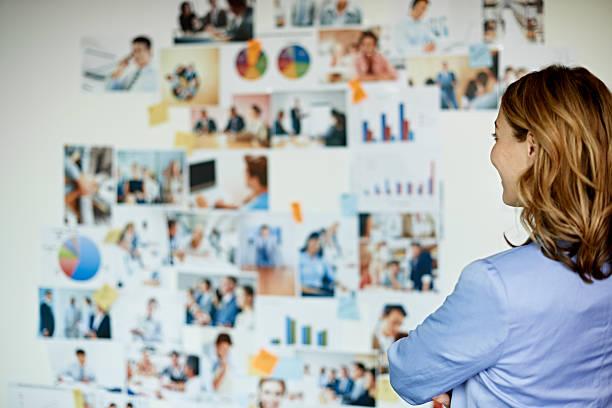 businesswoman looking at wall with photos - wandbilder selbst gestalten stock-fotos und bilder