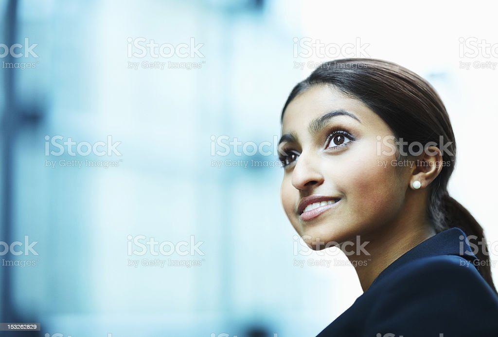 Businesswoman looking away and smiling Close-up of a businesswoman looking away and smiling 20-24 Years Stock Photo