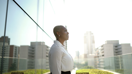 Businesswoman looking away contemplating and thinking on office rooftop