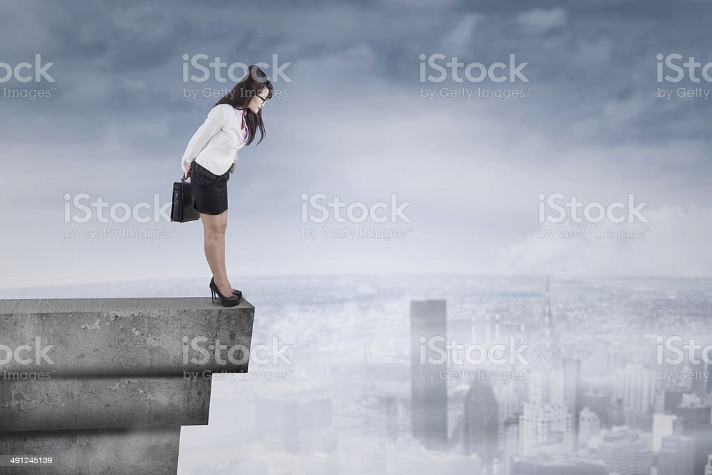 Businesswoman looking down from the rooftop stock photo