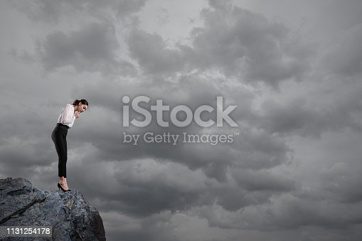Businesswoman about to step off of a clif
