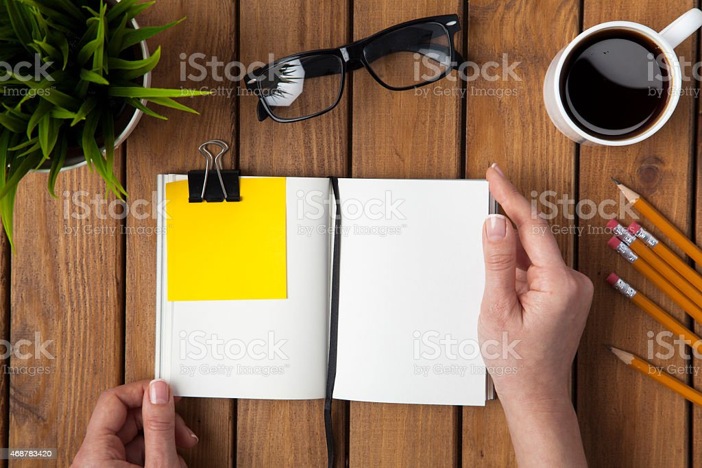 Businesswoman looking empty notebook pages on wooden desk stock photo