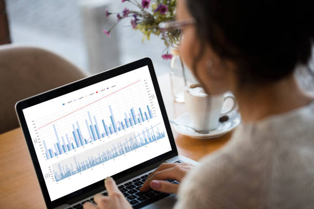 Businesswoman looking Financial Charts on laptop
