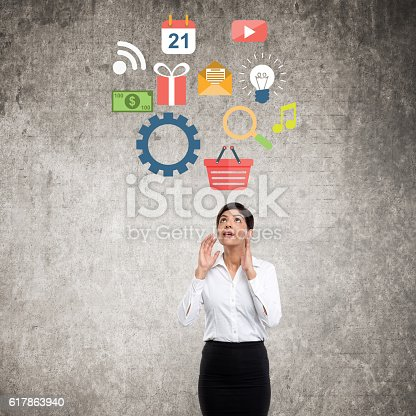 Young businesswoman standing in front of wall and looking infographic concept on wall.