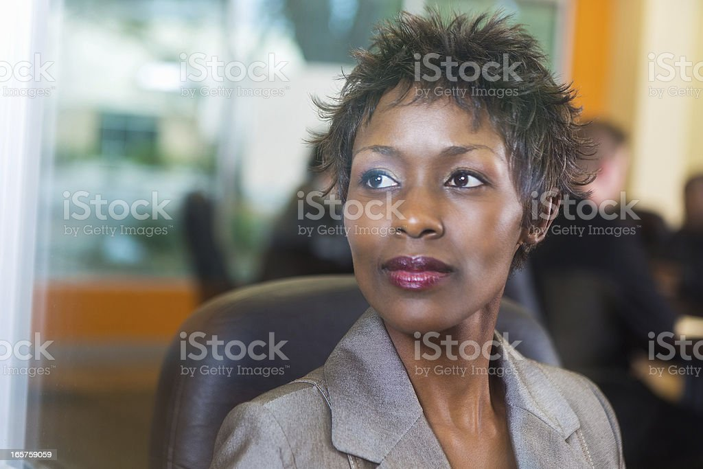 Businesswoman looking out conference room window during business meeting royalty-free stock photo
