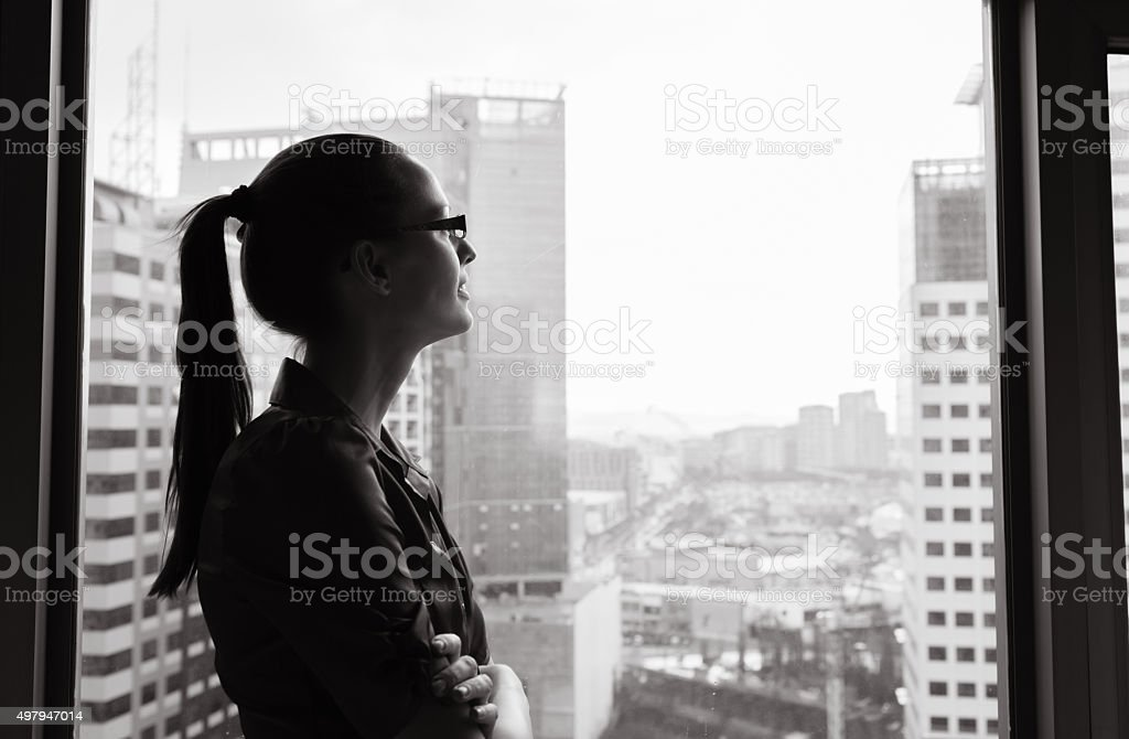 Businesswoman looking out the window stock photo