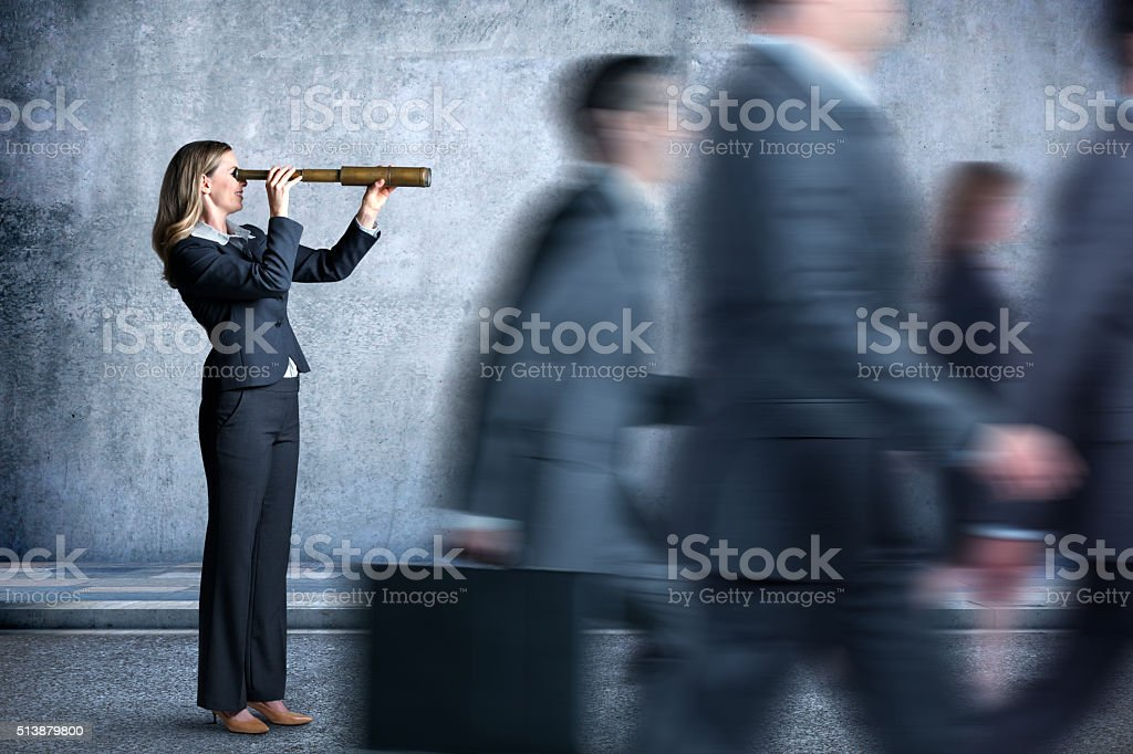 Businesswoman Looking Through Spyglass In The Direction Everyone Is Walking stock photo