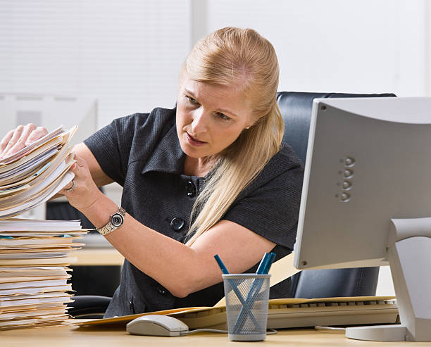 Businesswoman looking through stack of paperwork stock photo