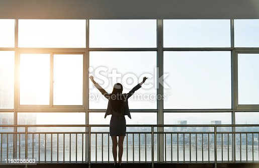 Businesswoman looking through the window with arms raised.