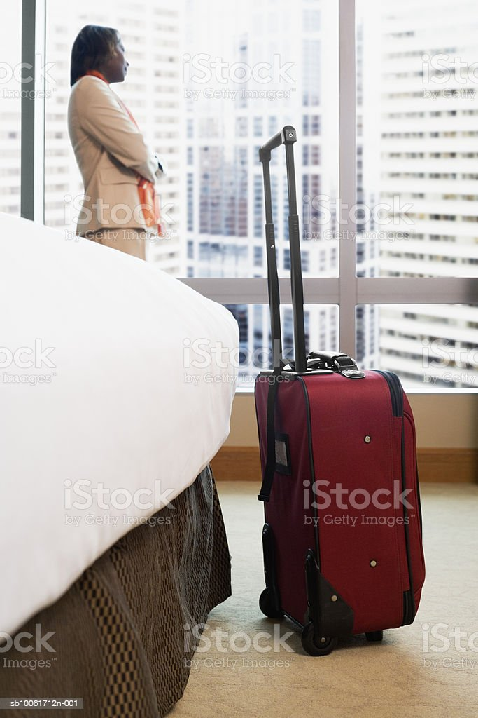 Businesswoman looking through window of hotel room royalty free stockfoto