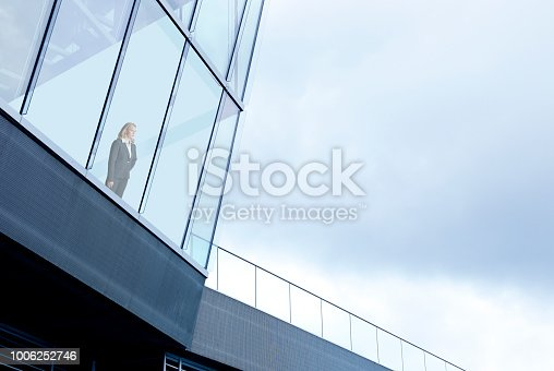 A businesswoman stands inside a large office building and looks through the window into the distance. The overcast sky provides ample room for copy and text.